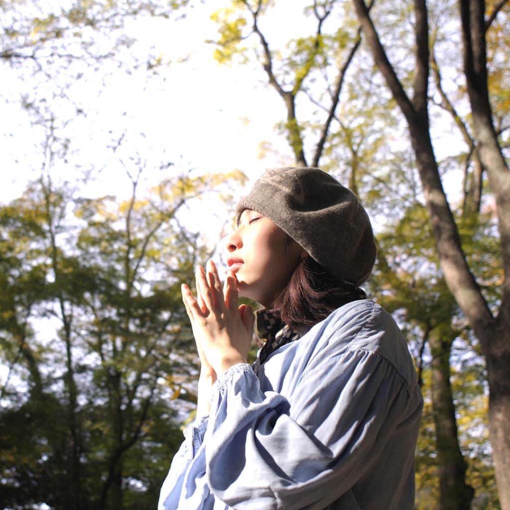 Asian woman praying, visualizing, and meditating in nature