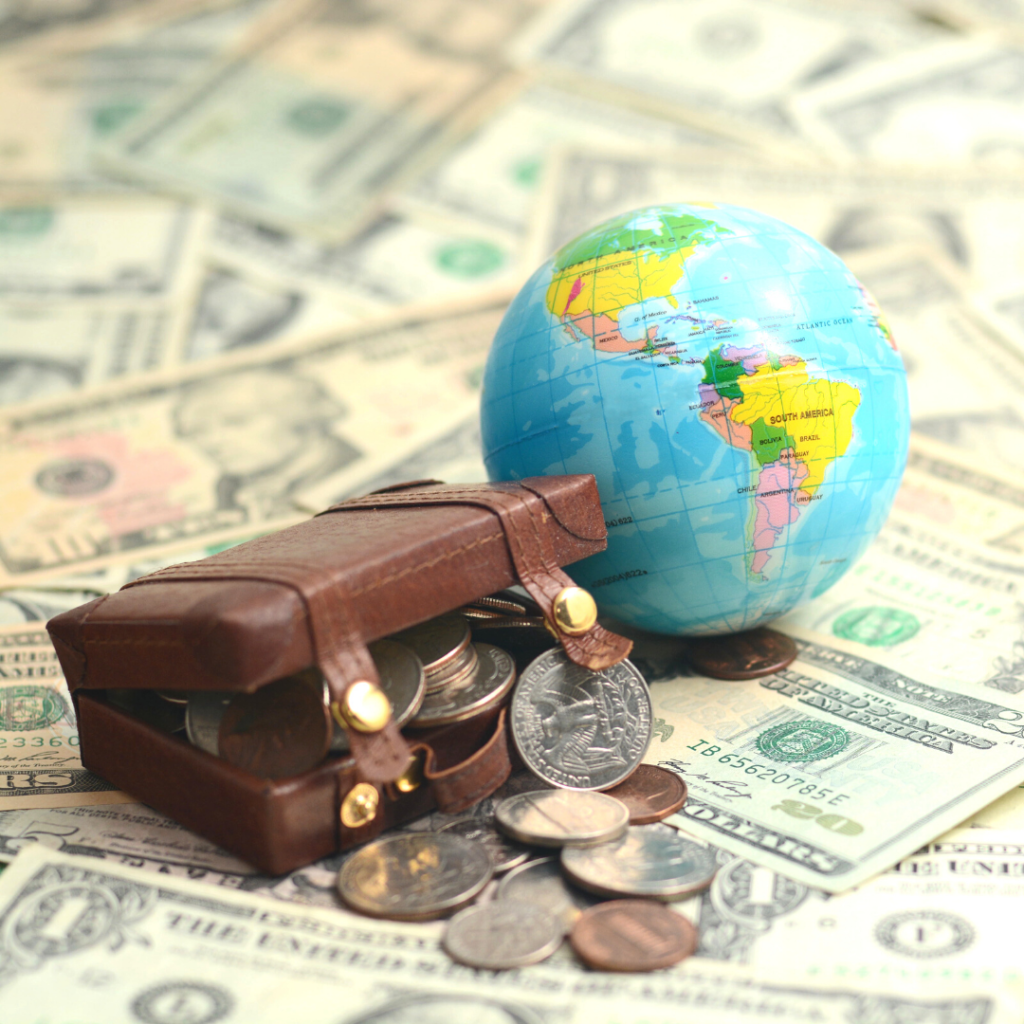 coins in a small luggage bag beside a globe with dollars background