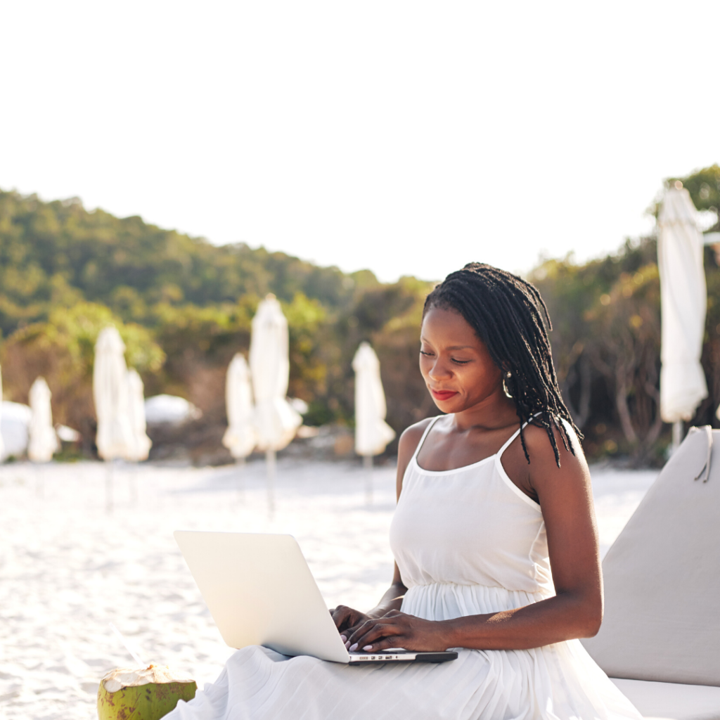 woman sitting in sun lounger with a laptop on her lap