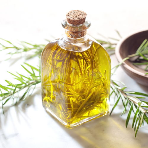 Rosemary Oil in a fancy bottle with fresh sprigs and plate