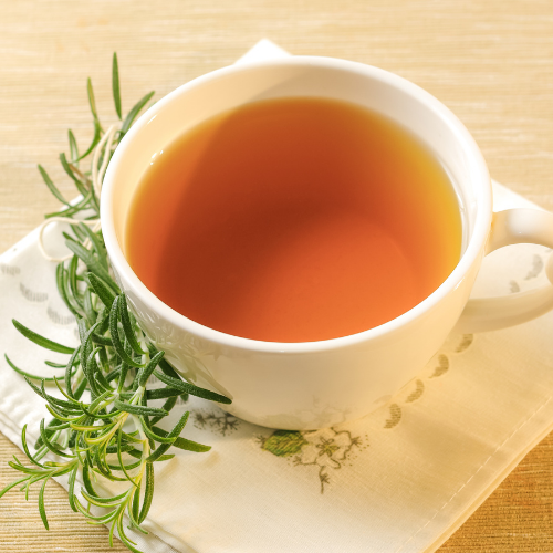 Rosemary Tea in a white cup with hot water and fresh rosemary sprigs