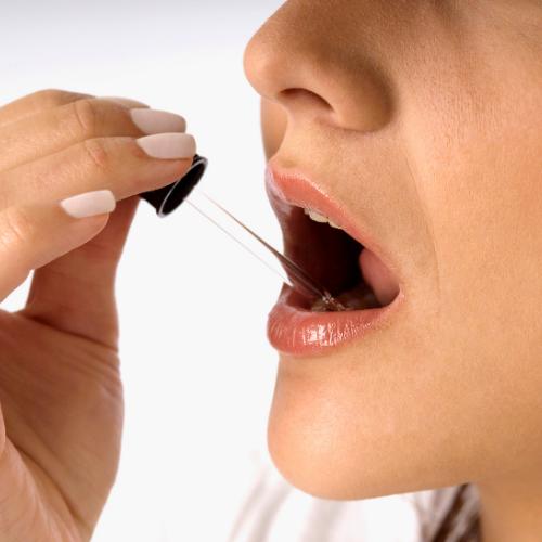women taking Oregano Drops under the tongue